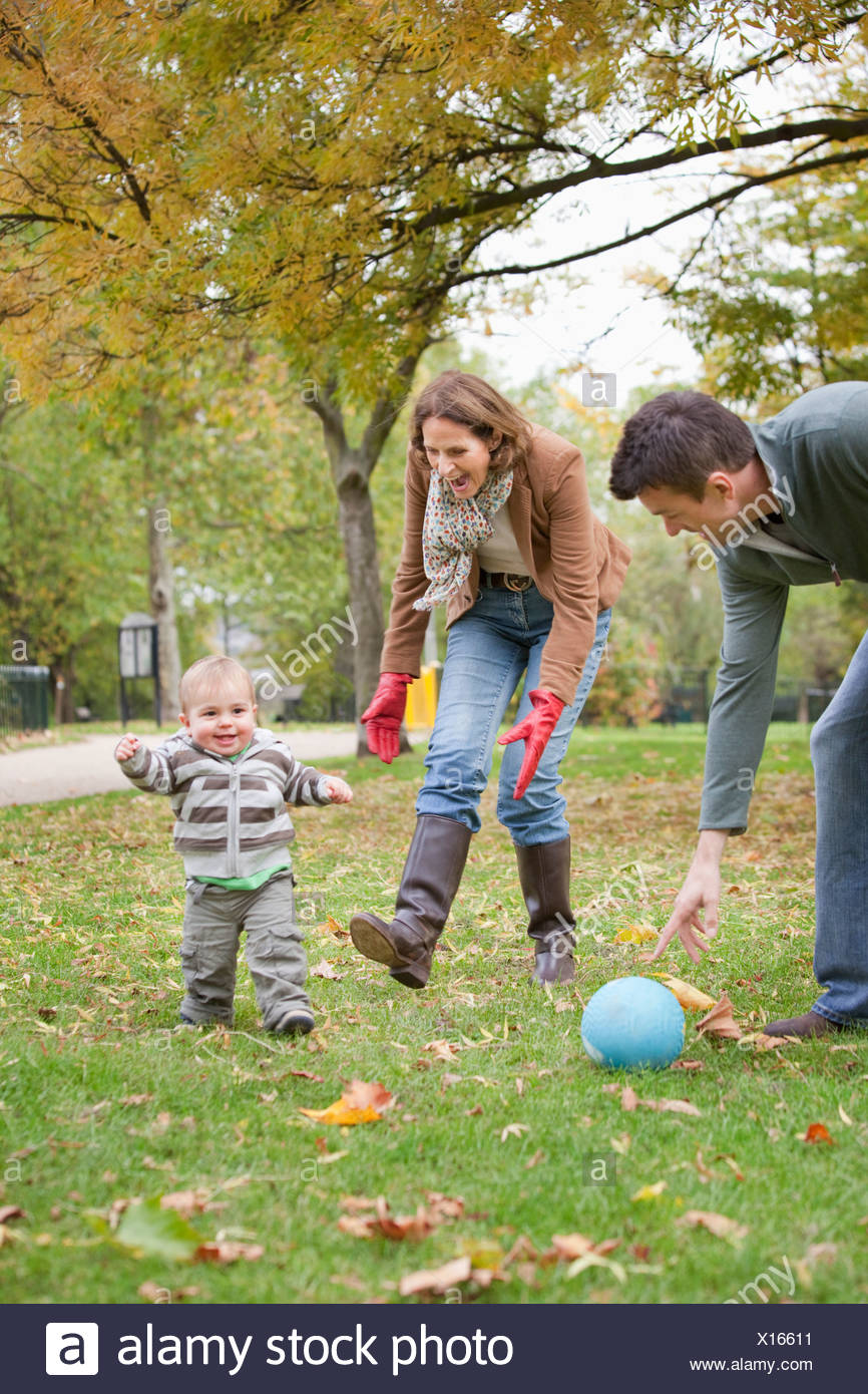 Family play soccer in the park - Stock Image