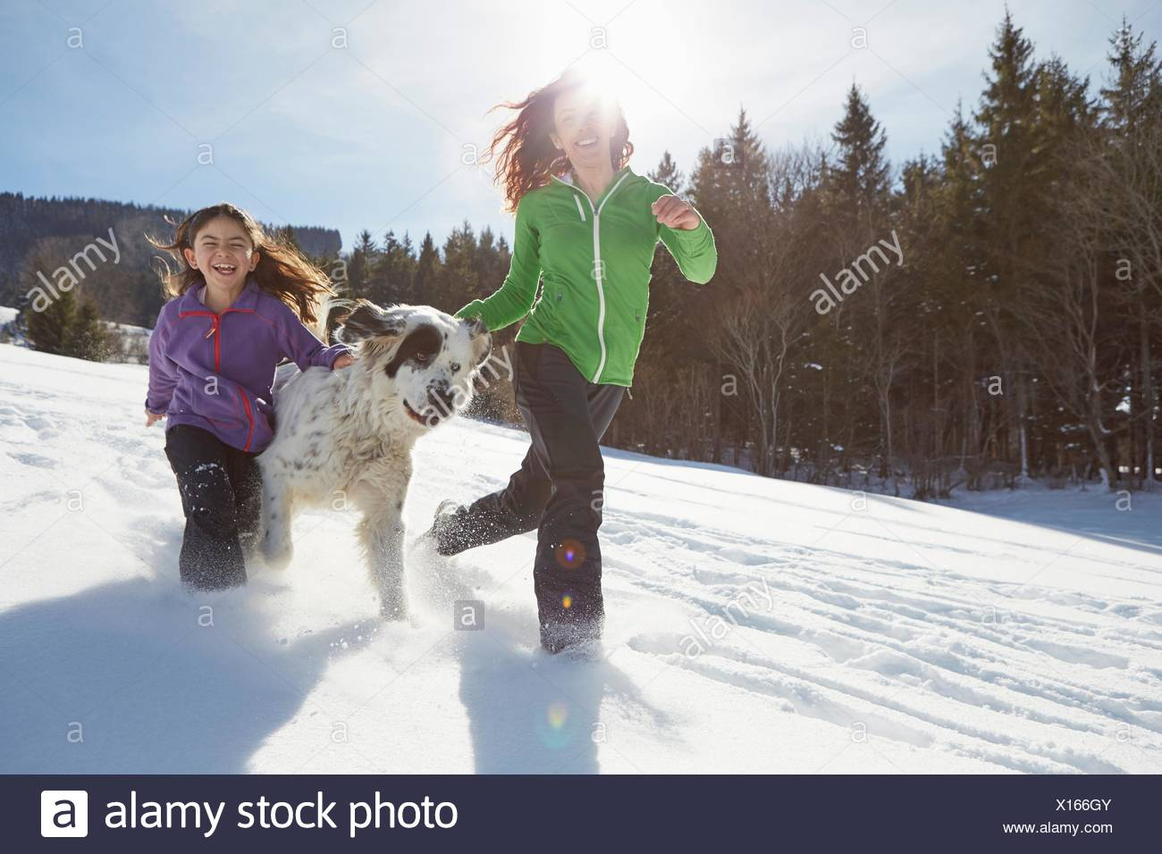 Mother and daughter running with their pet dog - Stock Image