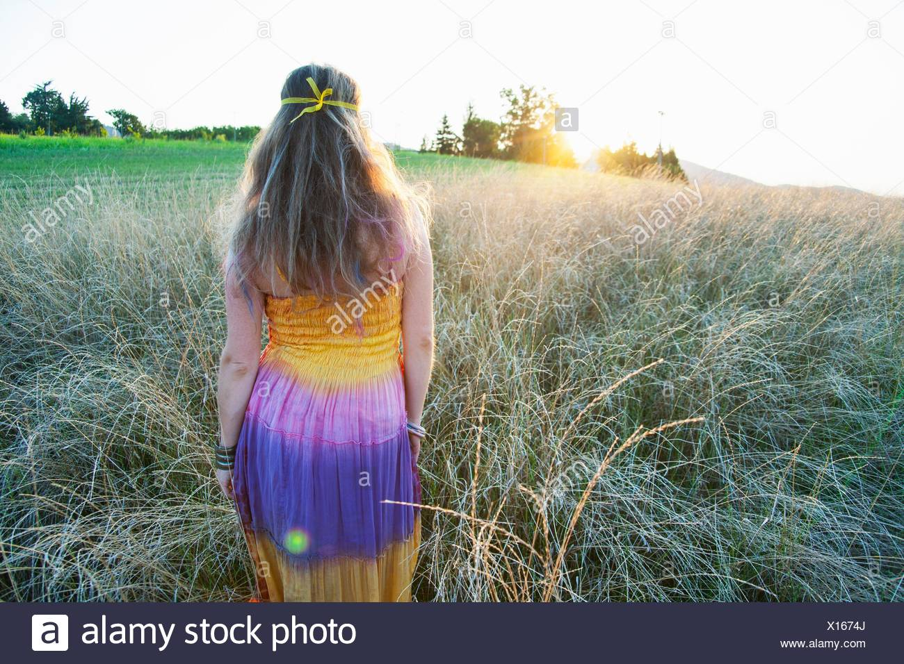 b0aa2477 Portrait of mid adult woman wearing hippy clothes, walking through field at  sunset, rear view