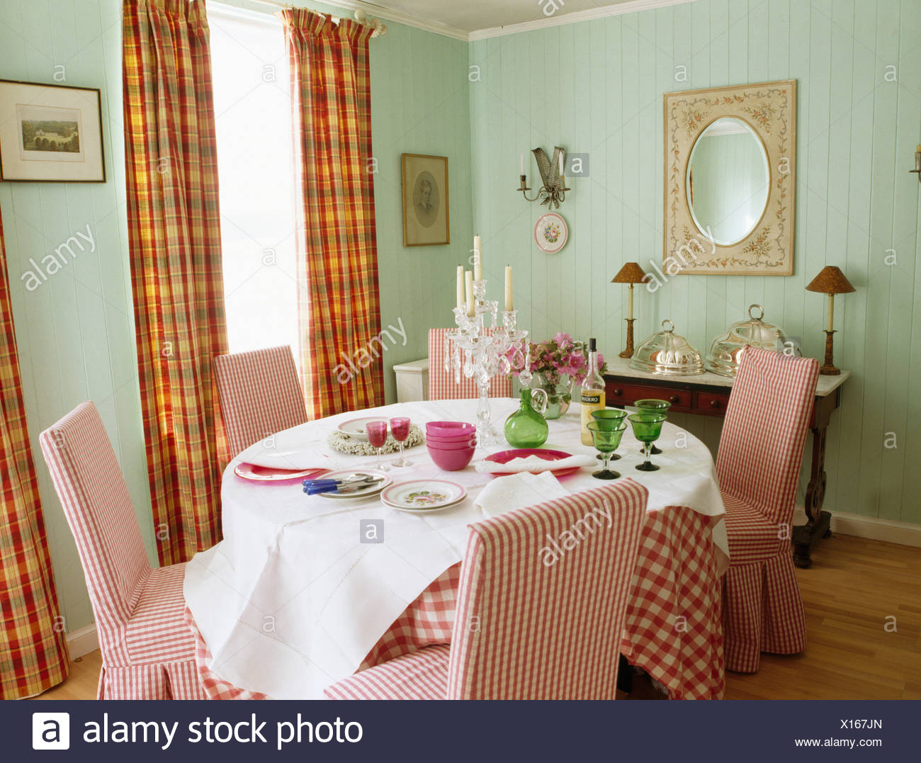 Red Checked Loose Covers On Chairs At Table With White Linen Cloth In Pale Green Dining Room With Orange Checked Curtains Stock Photo Alamy