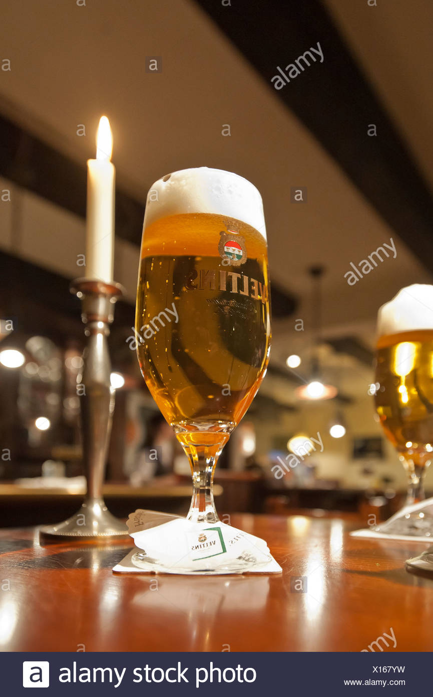 Pils or Pilsener beer on a bar next to a candle, Greetsiel, East Frisia, Lower Saxony, Germany, Europe - Stock Image