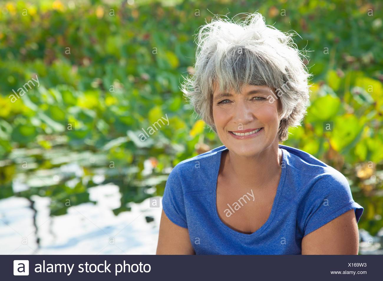 Portrait of mature woman, smiling, outdoors - Stock Image