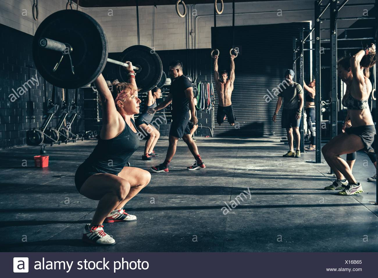 Woman crouching with barbell in gym - Stock Image