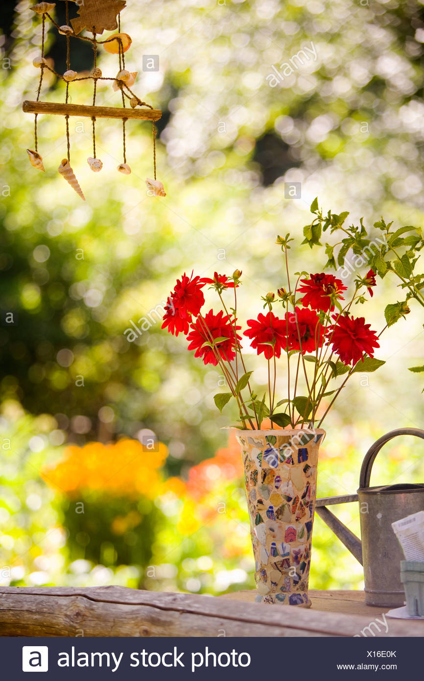 Watering can with a vase of flowers and a wind chime - Stock Image