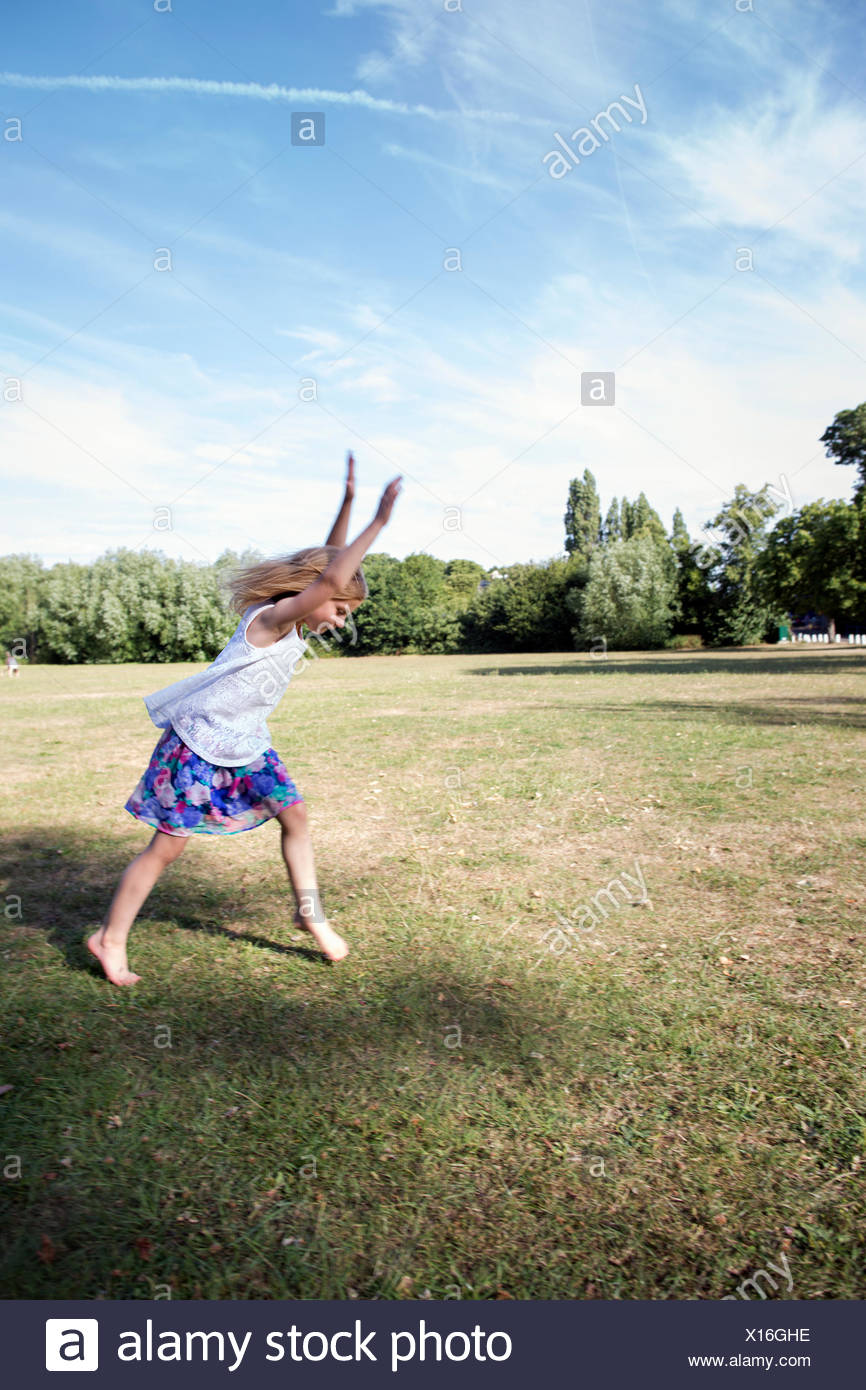 Young girl playing in a park, preparing to do a handstand. - Stock Image
