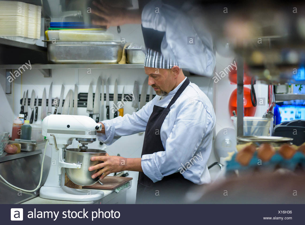 Chef mixes food in traditional Italian restaurant kitchen - Stock Image