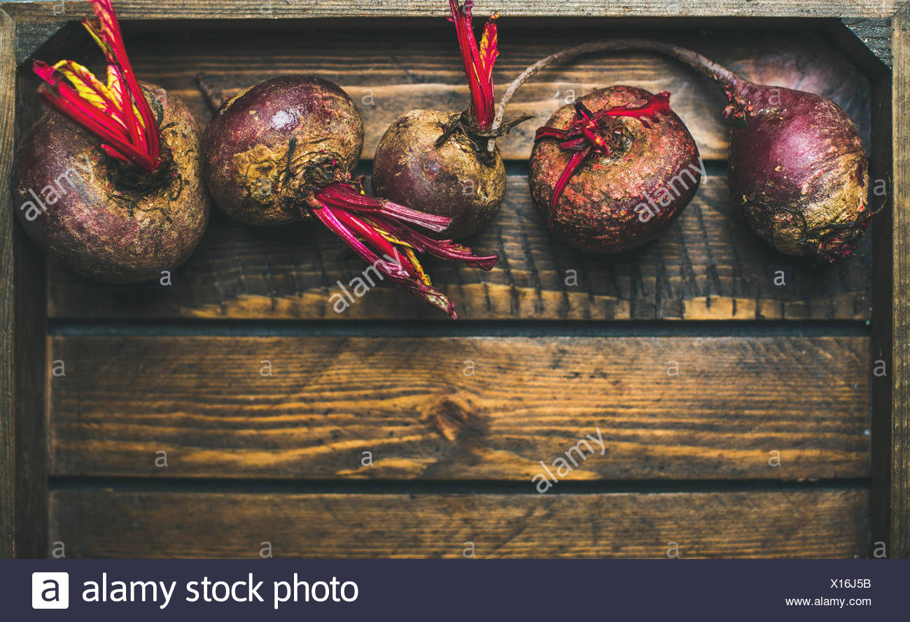Raw organic purple beetroots in rustic wooden box, selective fovus, top view, copy space - Stock Image