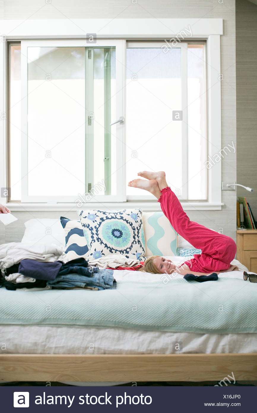 Portrait of girl lying on bed with legs raised - Stock Image