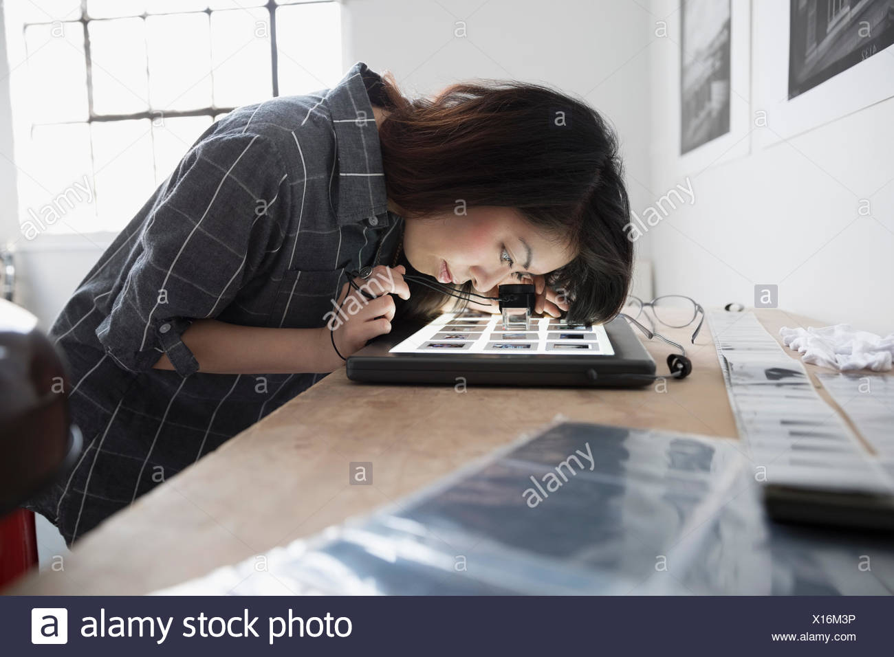 Female photographer reviewing photographic slides with magnifying loupe in art studio - Stock Image