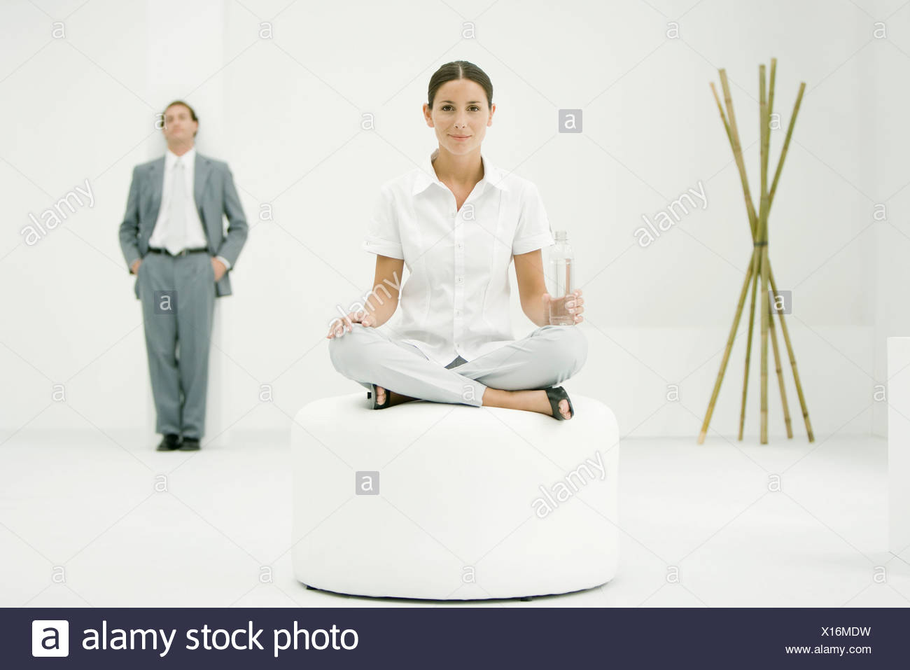 Professional woman sitting on ottoman, holding water bottle, businessman and bamboo in background Stock Photo
