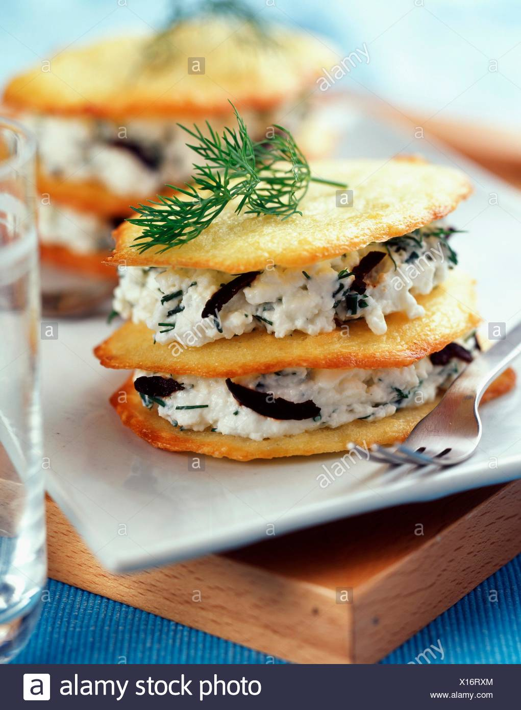 Layered thin cheese biscuits and fromage frais with olives - Stock Image