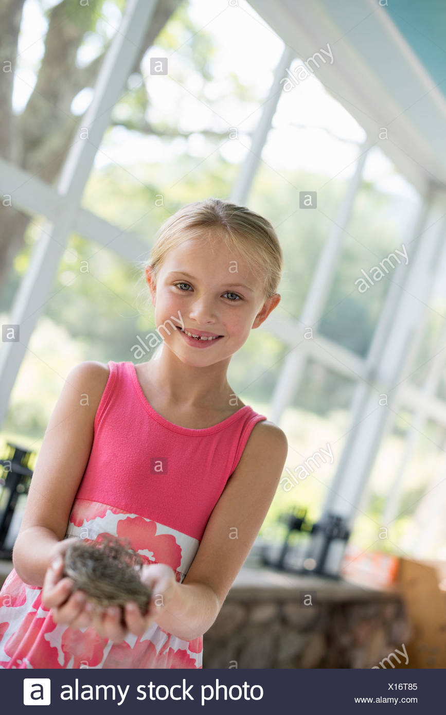 A young girl in a kitchen wearing a pink dress. Holding a bird's nest. - Stock Image