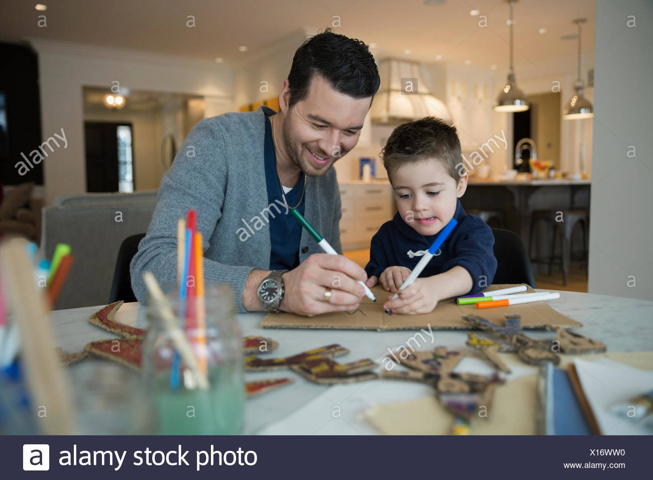 Father and son drawing with markers at table Stock Photo