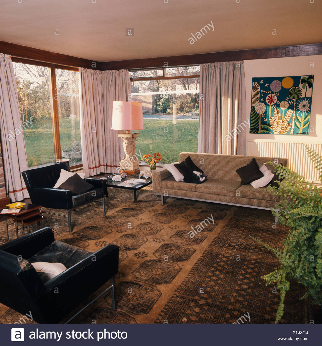 Black Leather Armchairs And Beige Sofa In Sixties Living Room With Brown Oriental Carpet And White Curtains On Large Windows Stock Photo Alamy