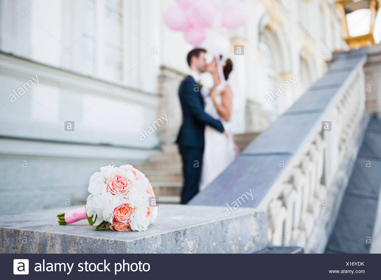 Mid adult bride and groom kissing on stairway - Stock Image