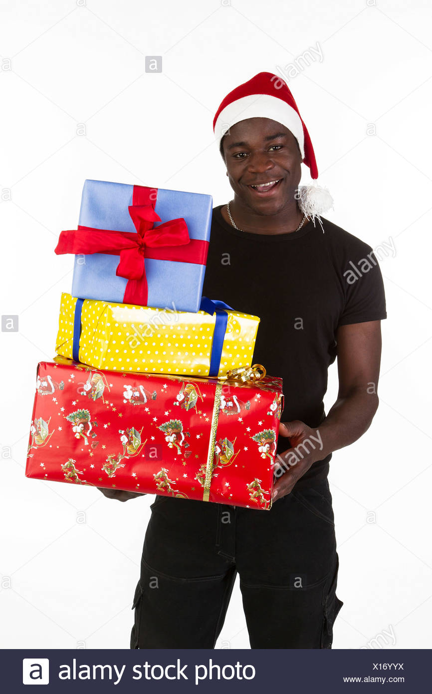 a458bd9570d49 Young black man wearing a Santa hat and holding presents - Stock Image
