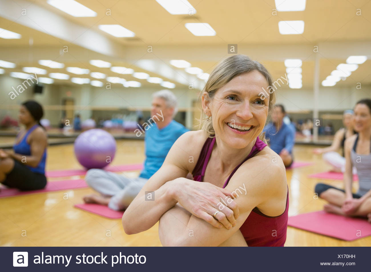 Smiling woman on yoga mat in exercise class - Stock Image