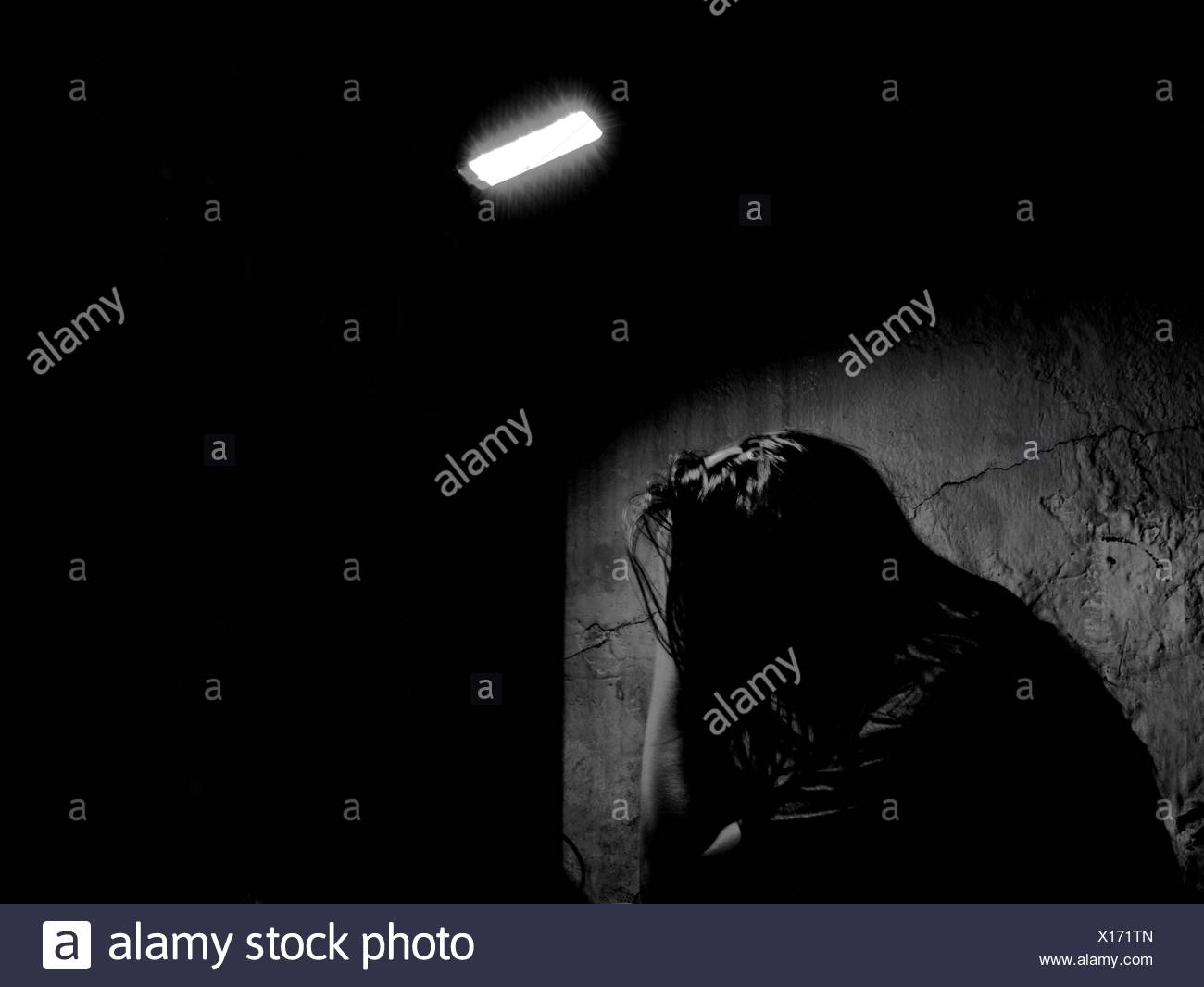 Depressed Woman With Head In Hands In Illuminated House - Stock Image