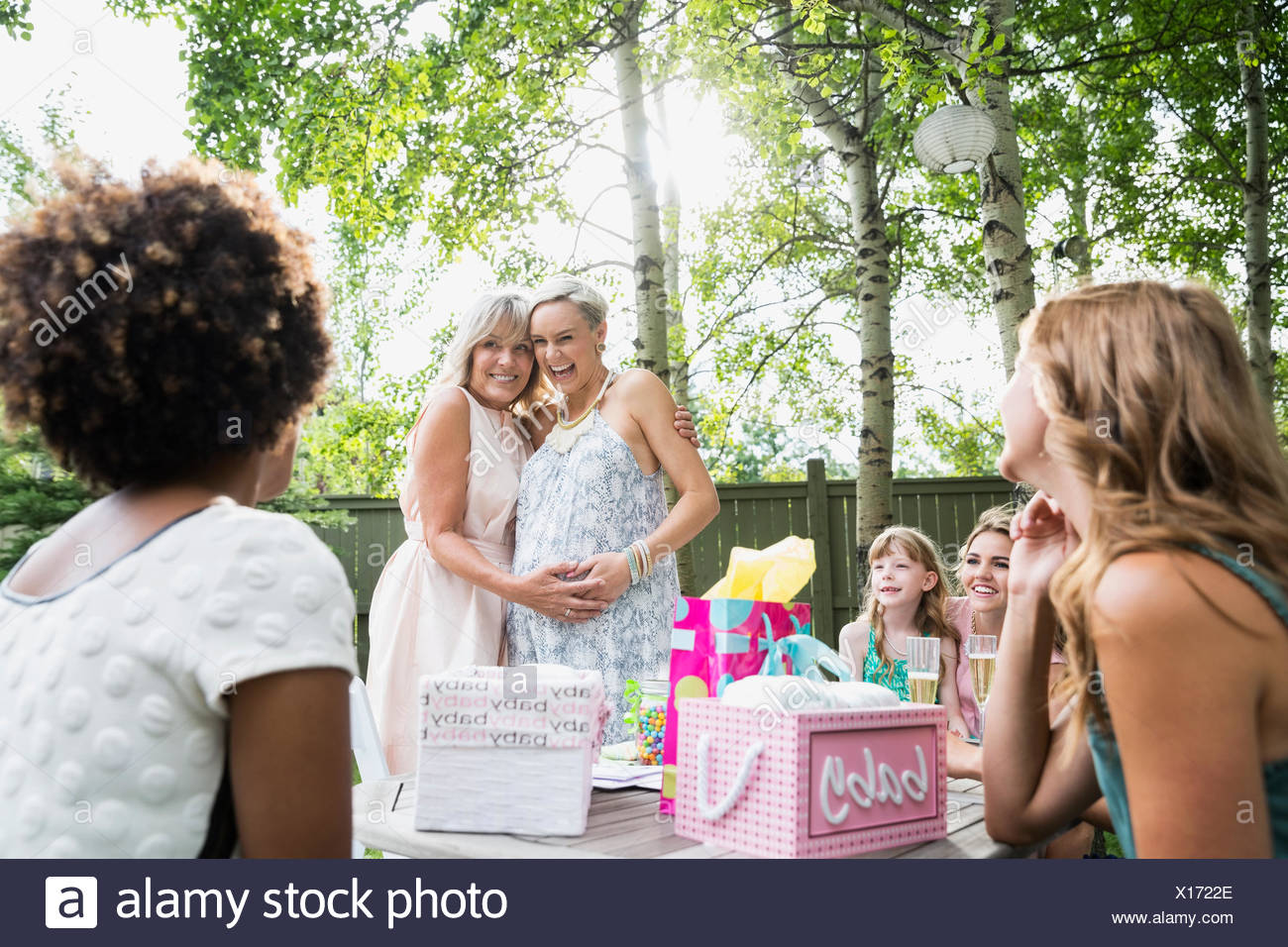 Mother and pregnant daughter hugging backyard baby shower Stock Photo