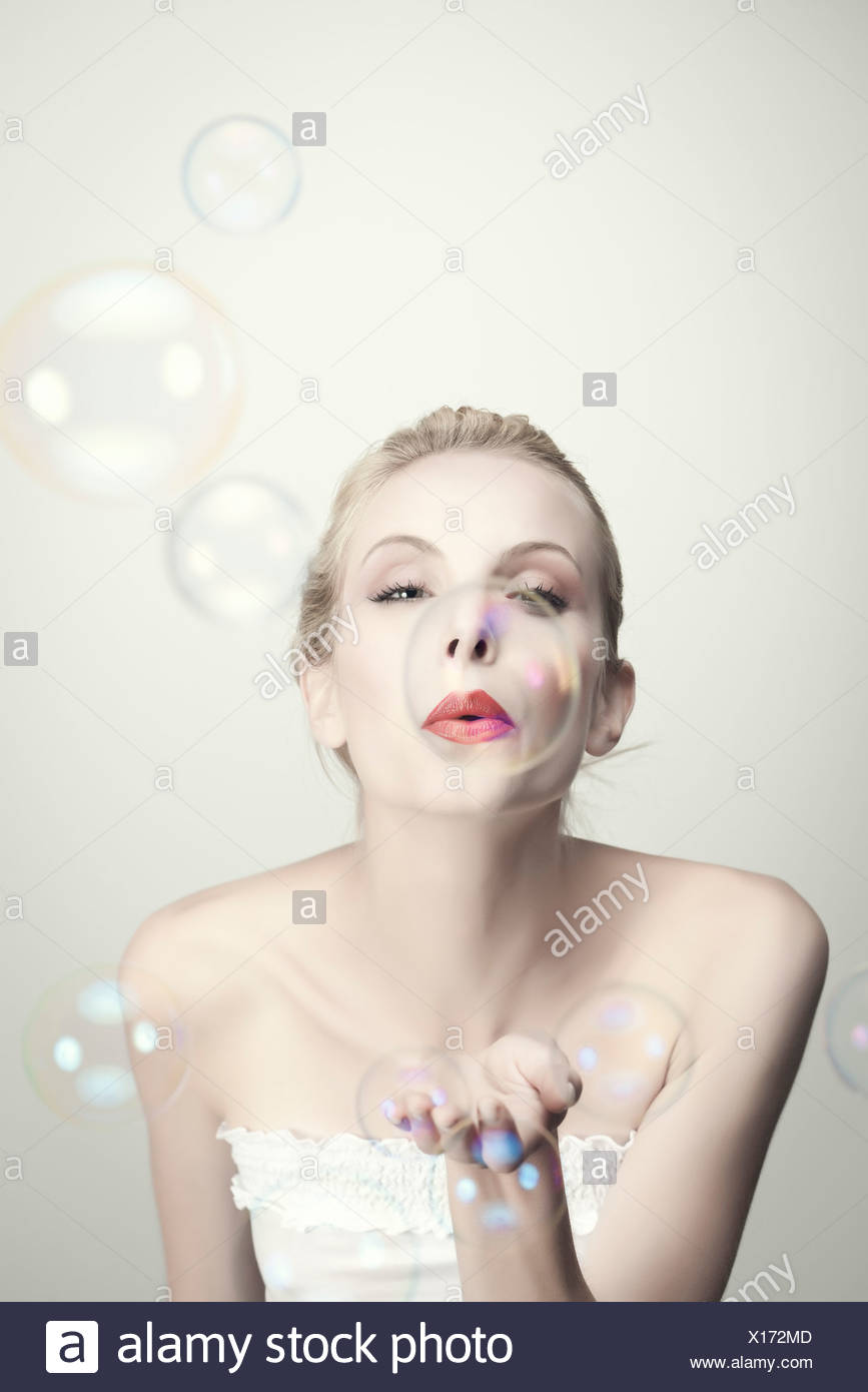 Young woman blowing bubbles - Stock Image