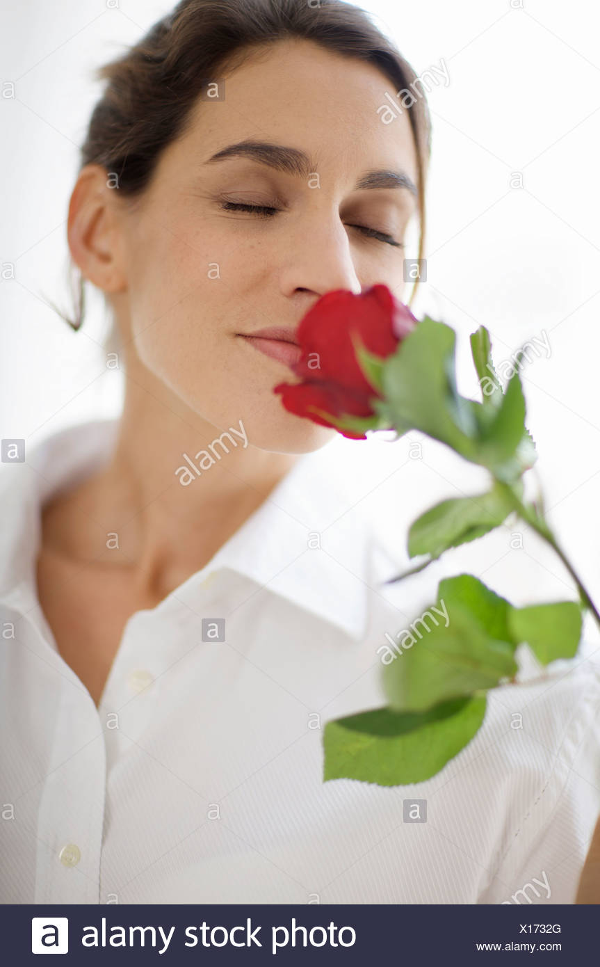 woman breathing in the scent of a rose - Stock Image