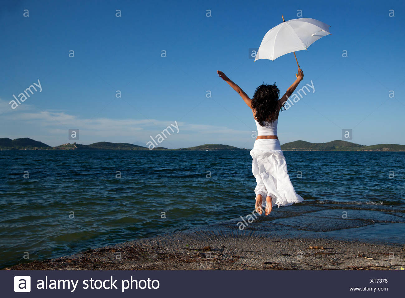 Young woman in white holding umbrella jumping on beach - Stock Image