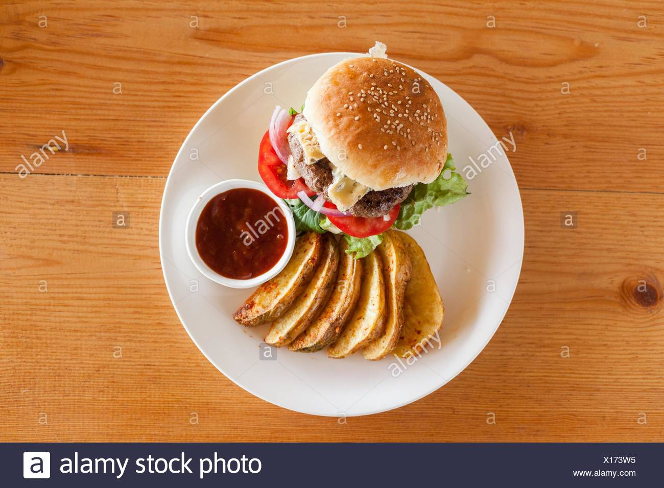 A Bleu (Blue) cheese hamburger with fries and barbecue sauce from above on a wood tabletop. Stock Photo