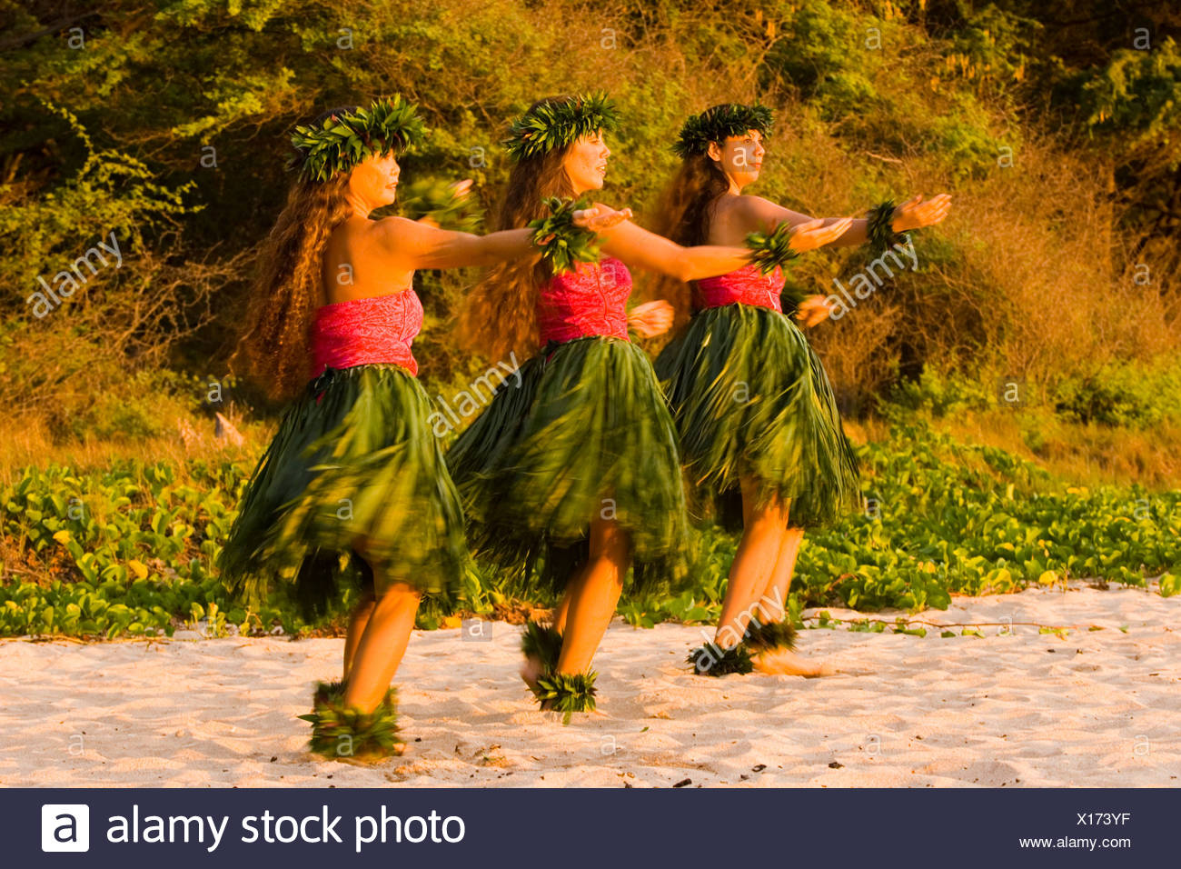 Three hula dancers in ti leaf skirts dance on the beach at sunset at Makena, Maui. - Stock Image