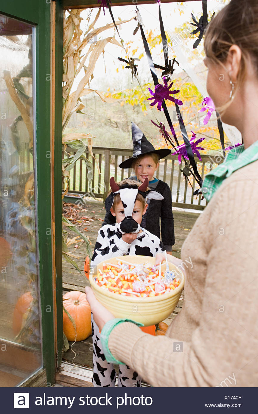 Woman with sweets for trick or treaters - Stock Image