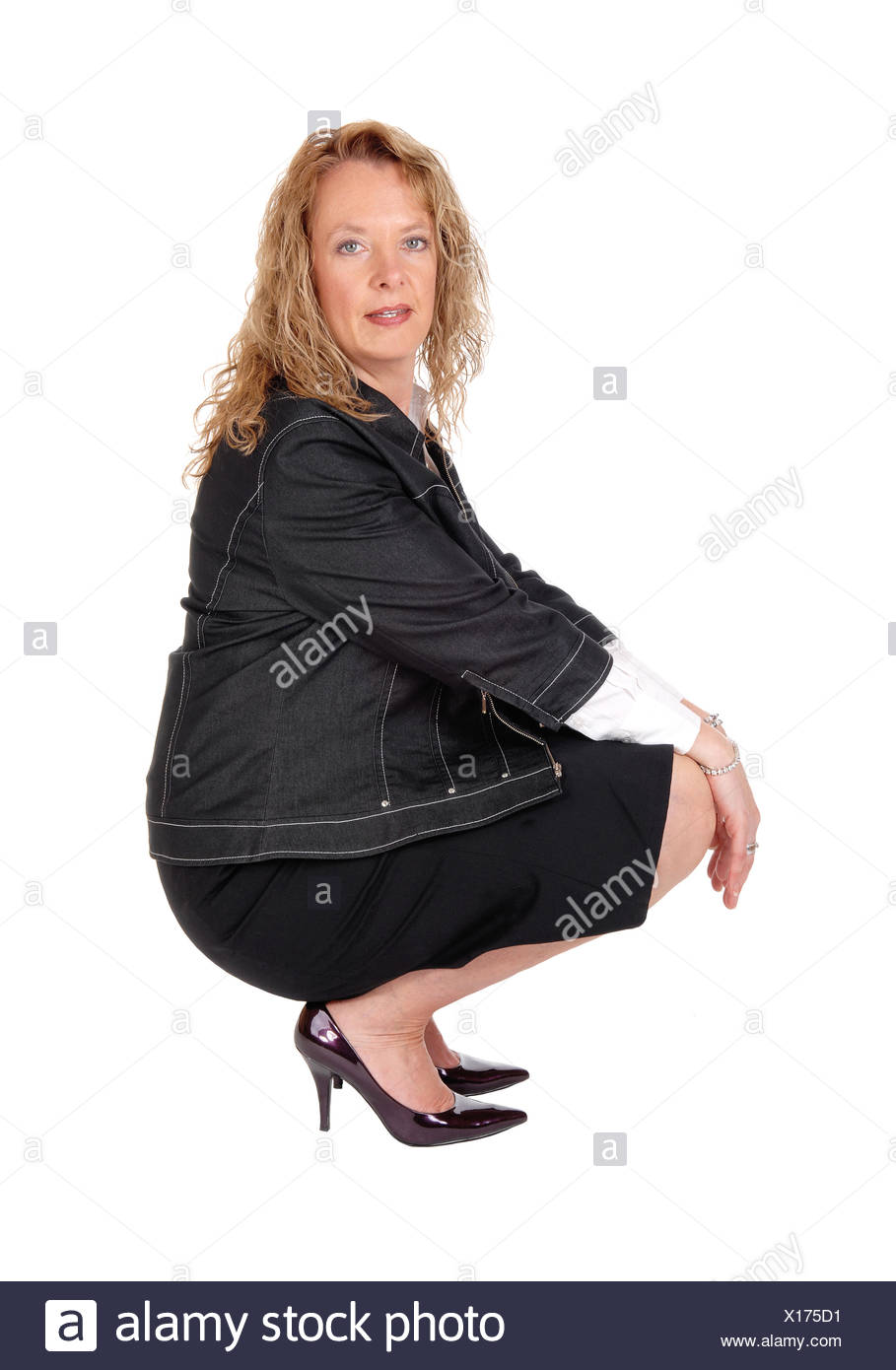 Lovely woman crouching on floor. - Stock Image