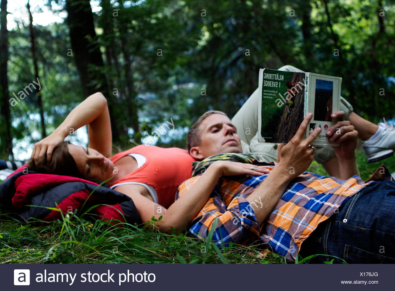 Sweden, Ostergotland, Agelsjon, Hikers lying on grass and reading guidebook - Stock Image