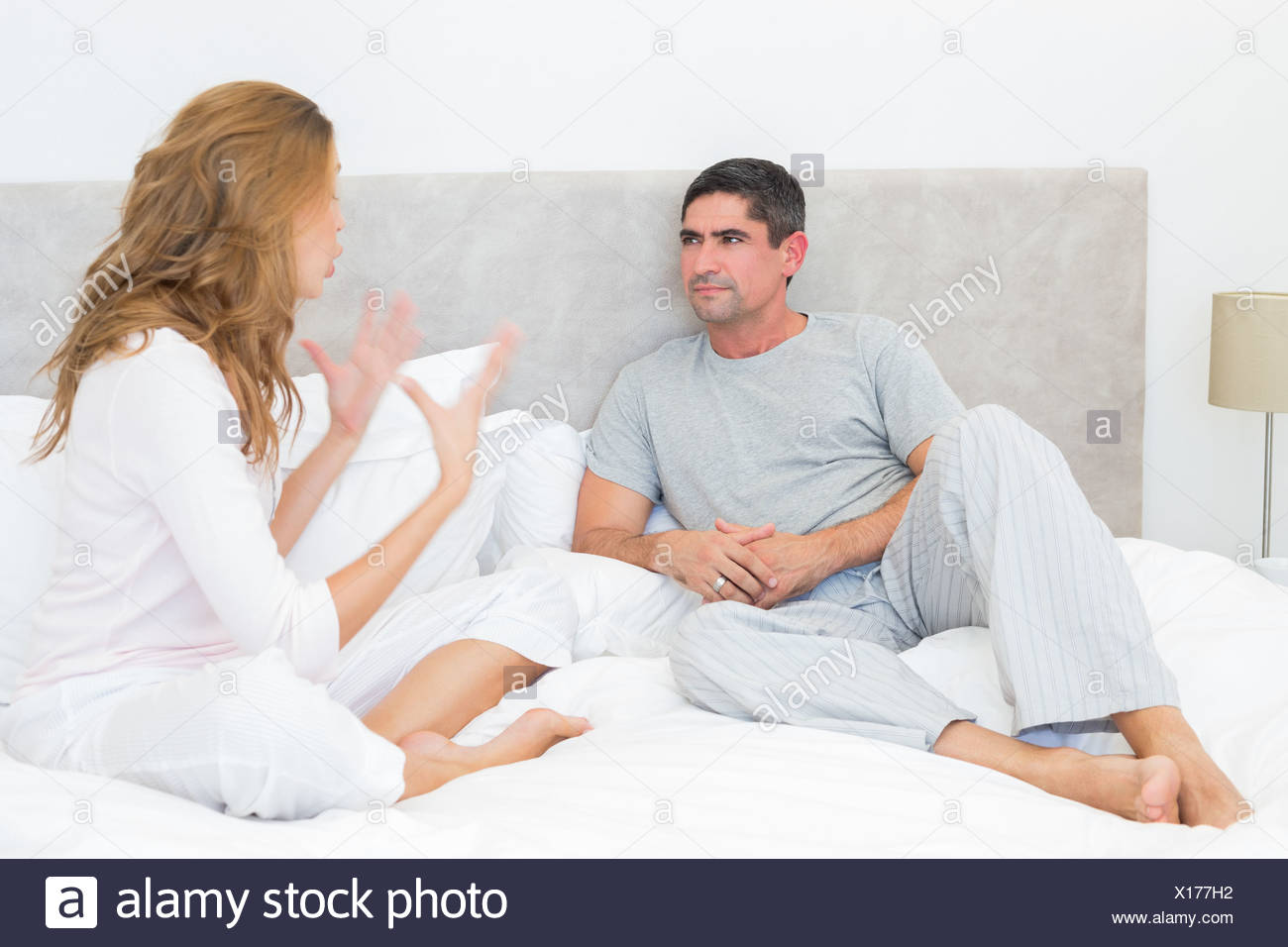 Couple arguing in bed - Stock Image