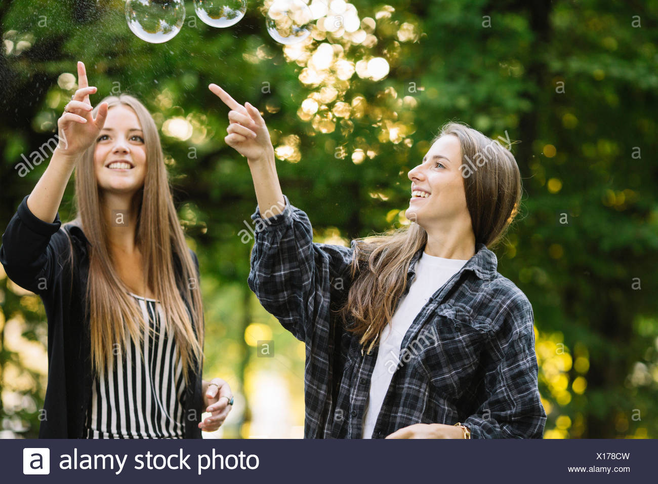 Two young female friends bursting floating bubbles in park - Stock Image