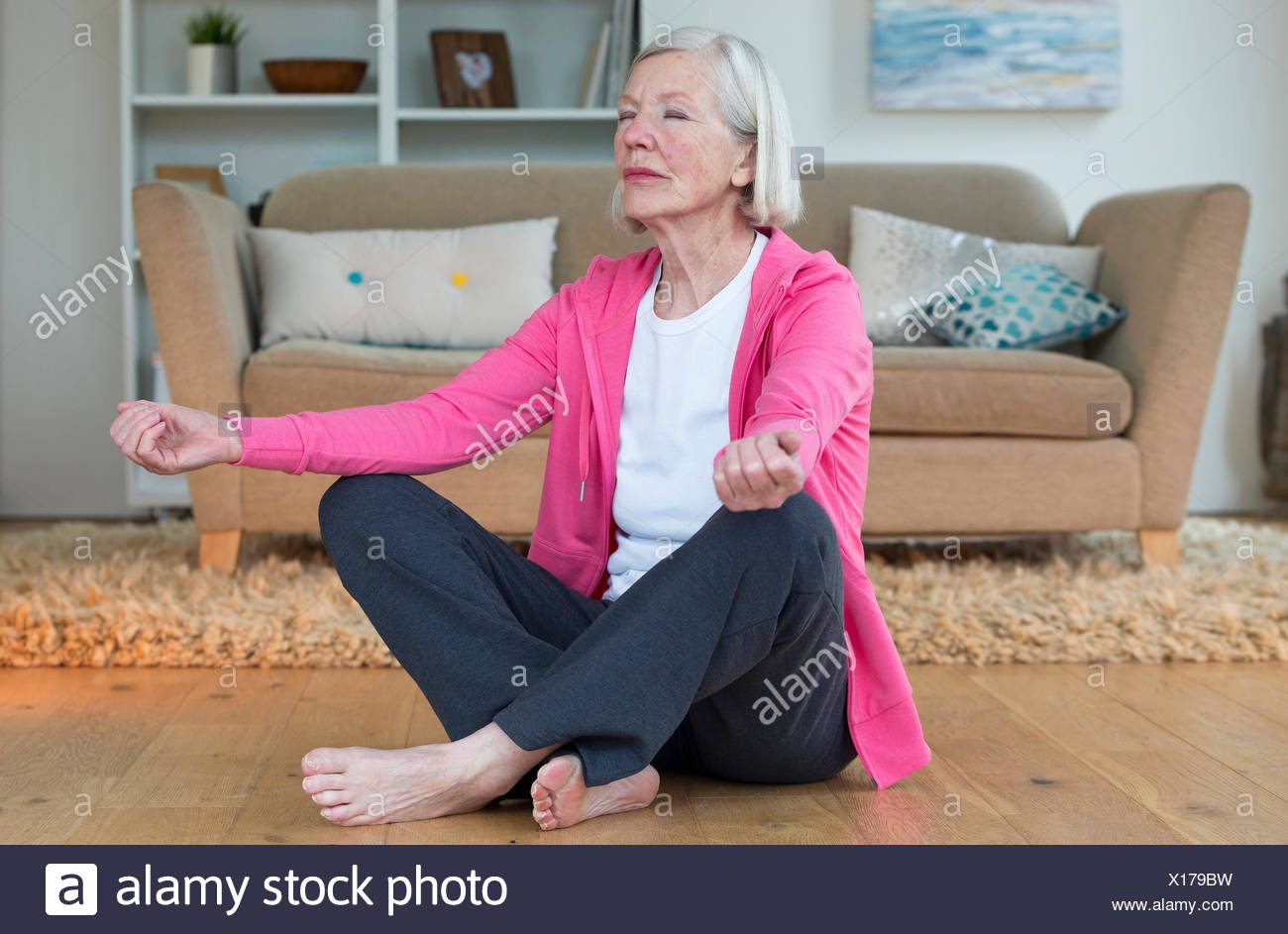 Elderly lady meditating at home Stock Photo