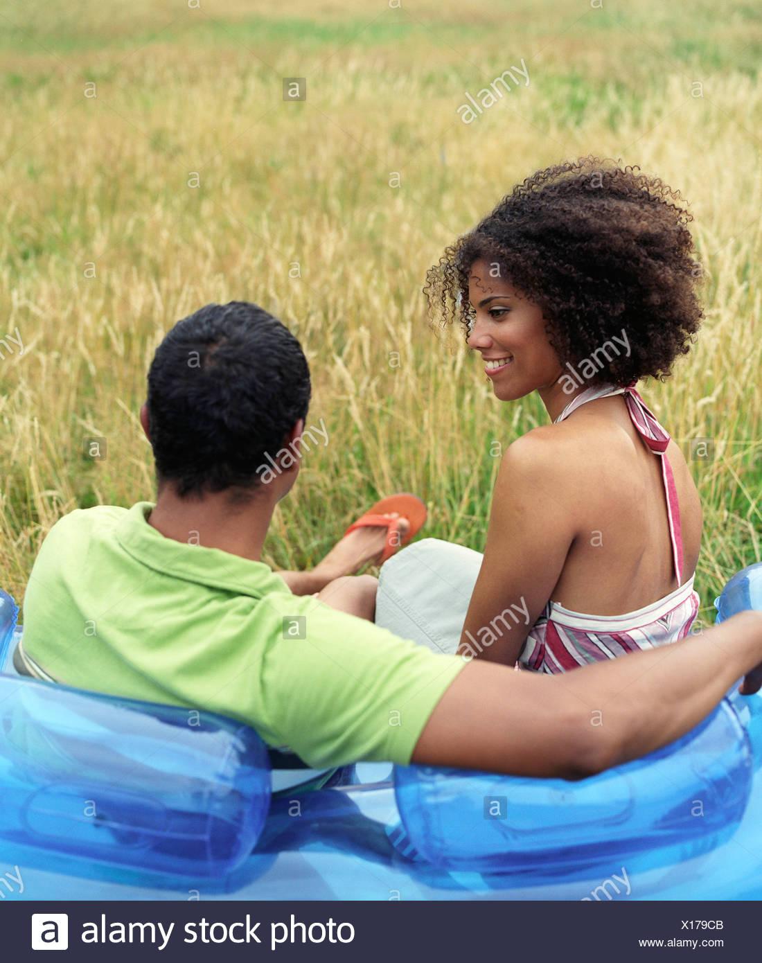 Couple sitting on blow up sofa outside - Stock Image
