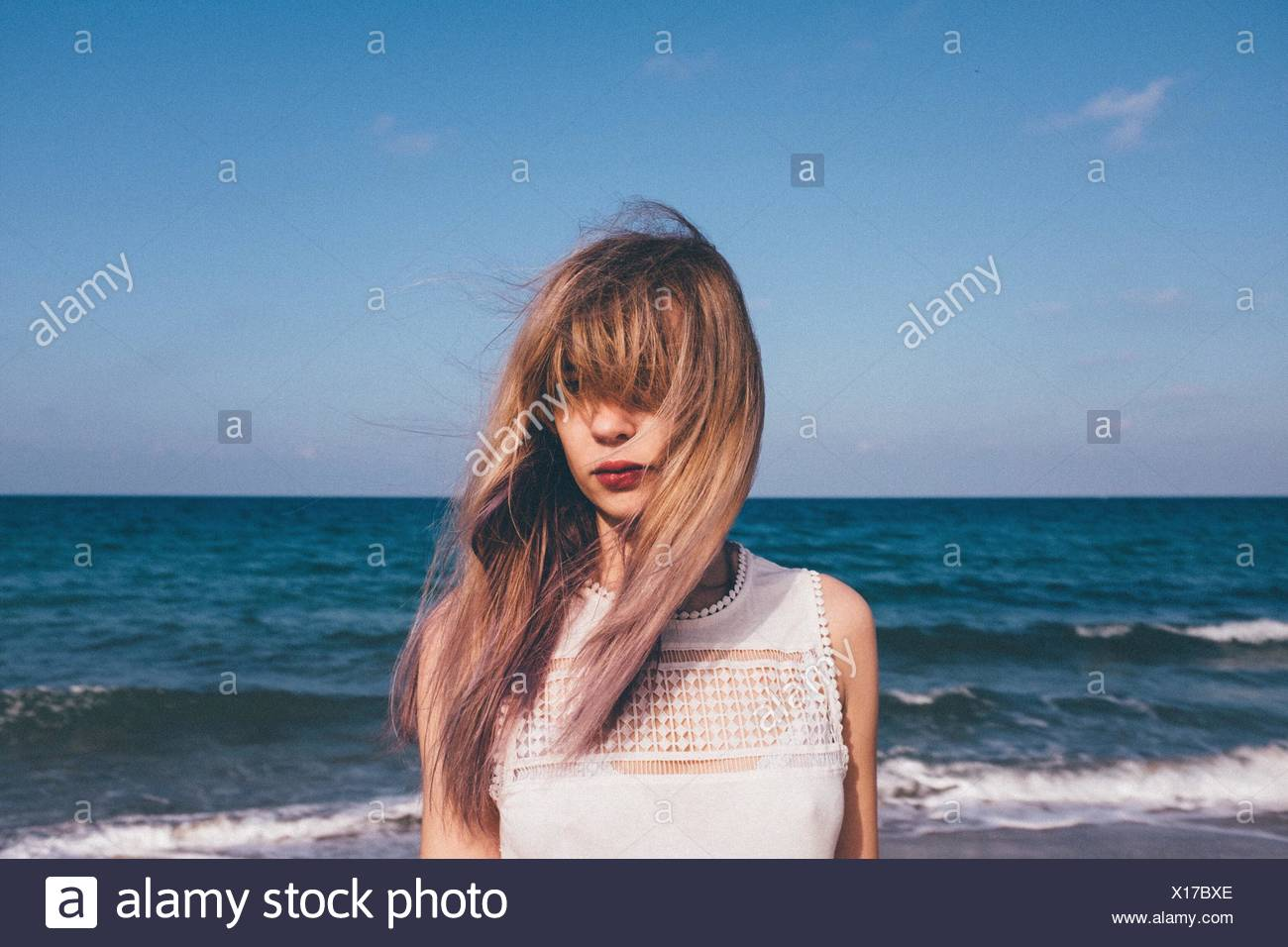 Front View Of Woman Standing At Sea Shore Against Sky - Stock Image
