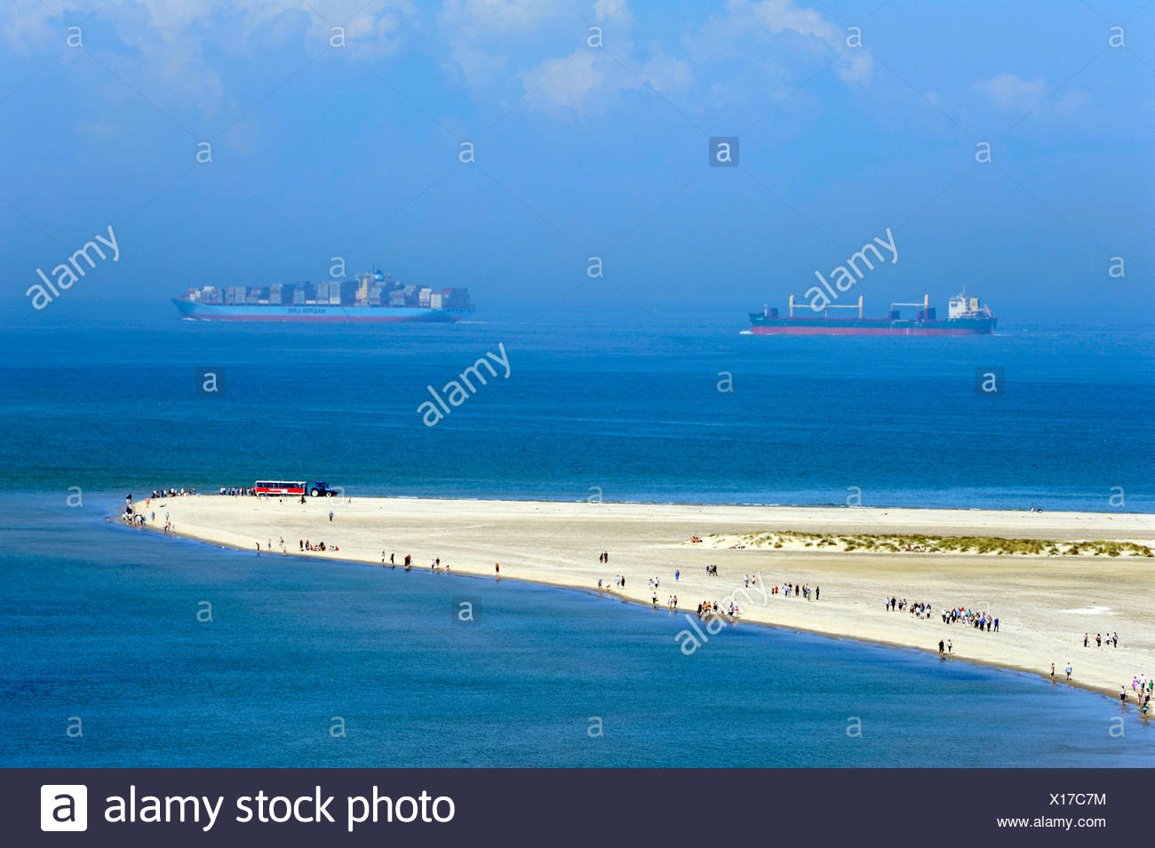 Headland with people where the North Sea and the Baltic Sea meet, container ships at back, Skagen, Jutland, Denmark, Europe - Stock Image