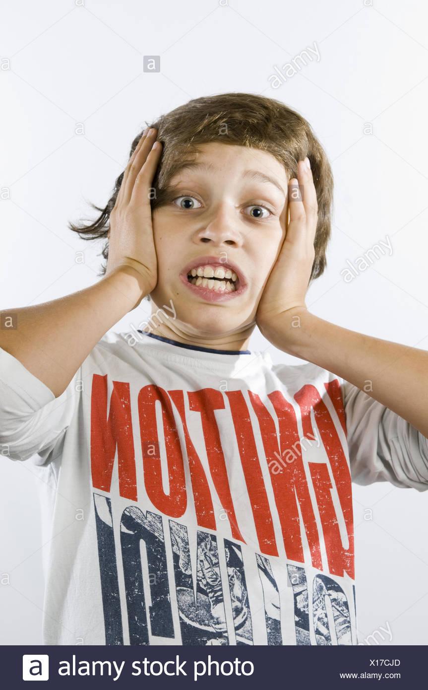 fearful grimacing of boy - Stock Image