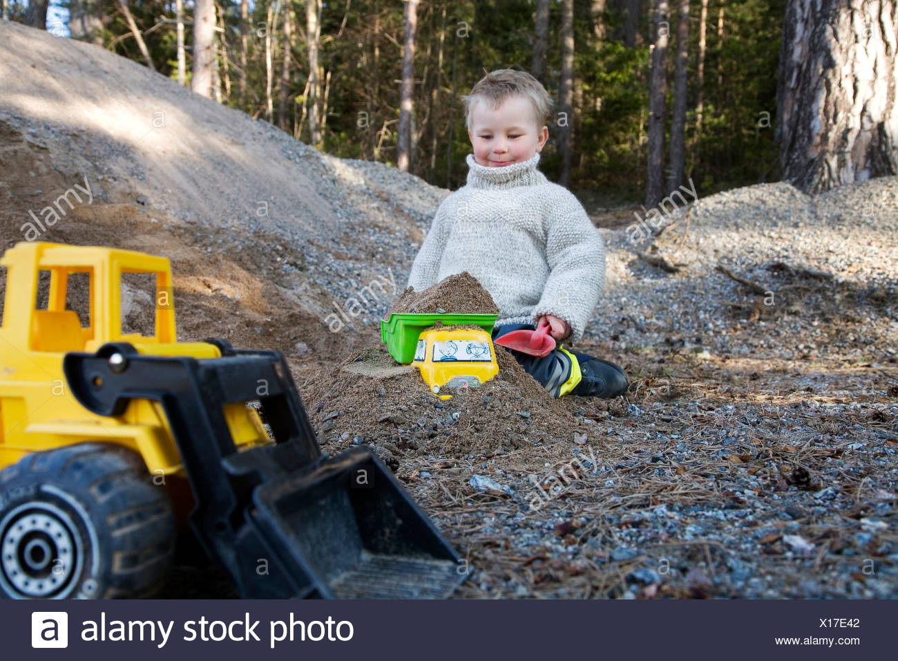 Little boy sitting in sandbox with cropped toy backhoe in foreground - Stock Image