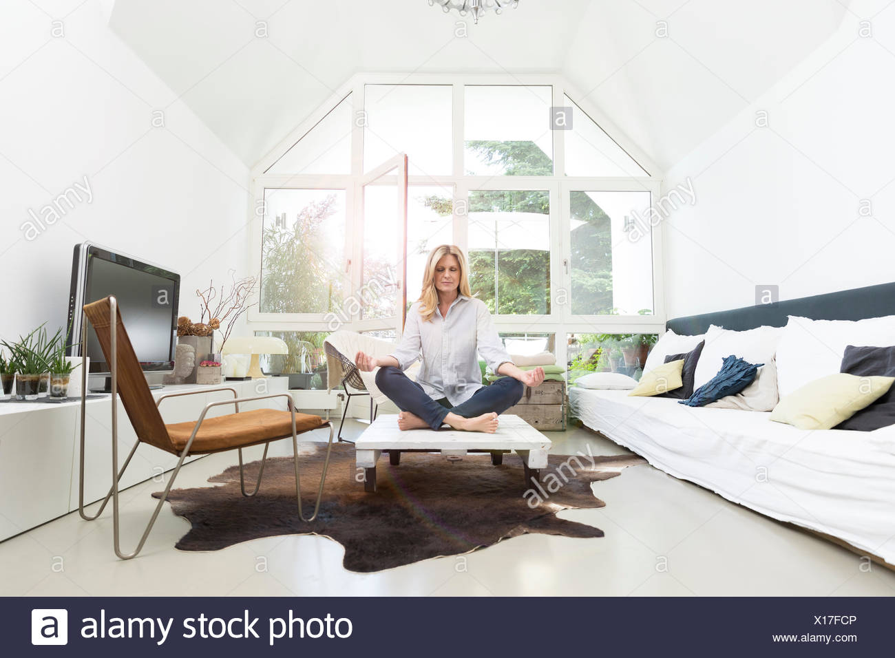 Blond woman sitting on coffee table, meditating - Stock Image