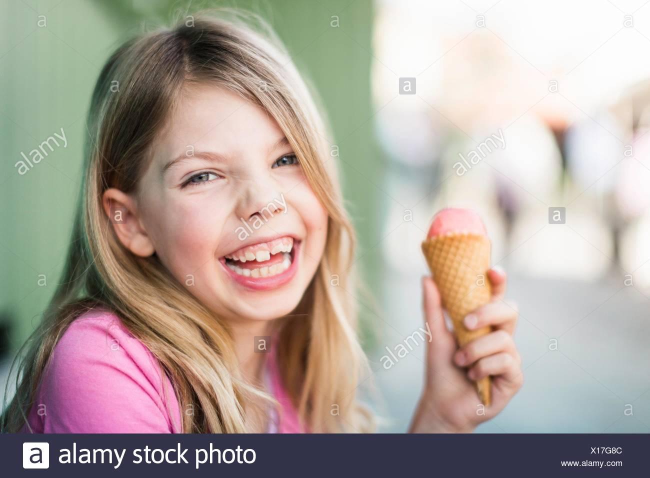 Portrait of young girl eating icecream - Stock Image