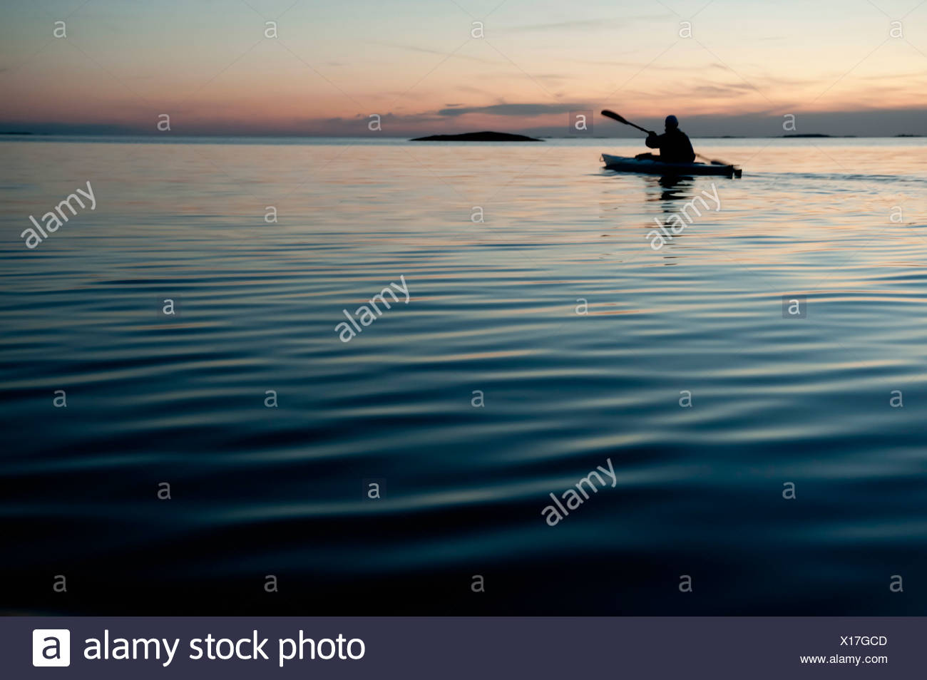 Silhouetted person oaring - Stock Image