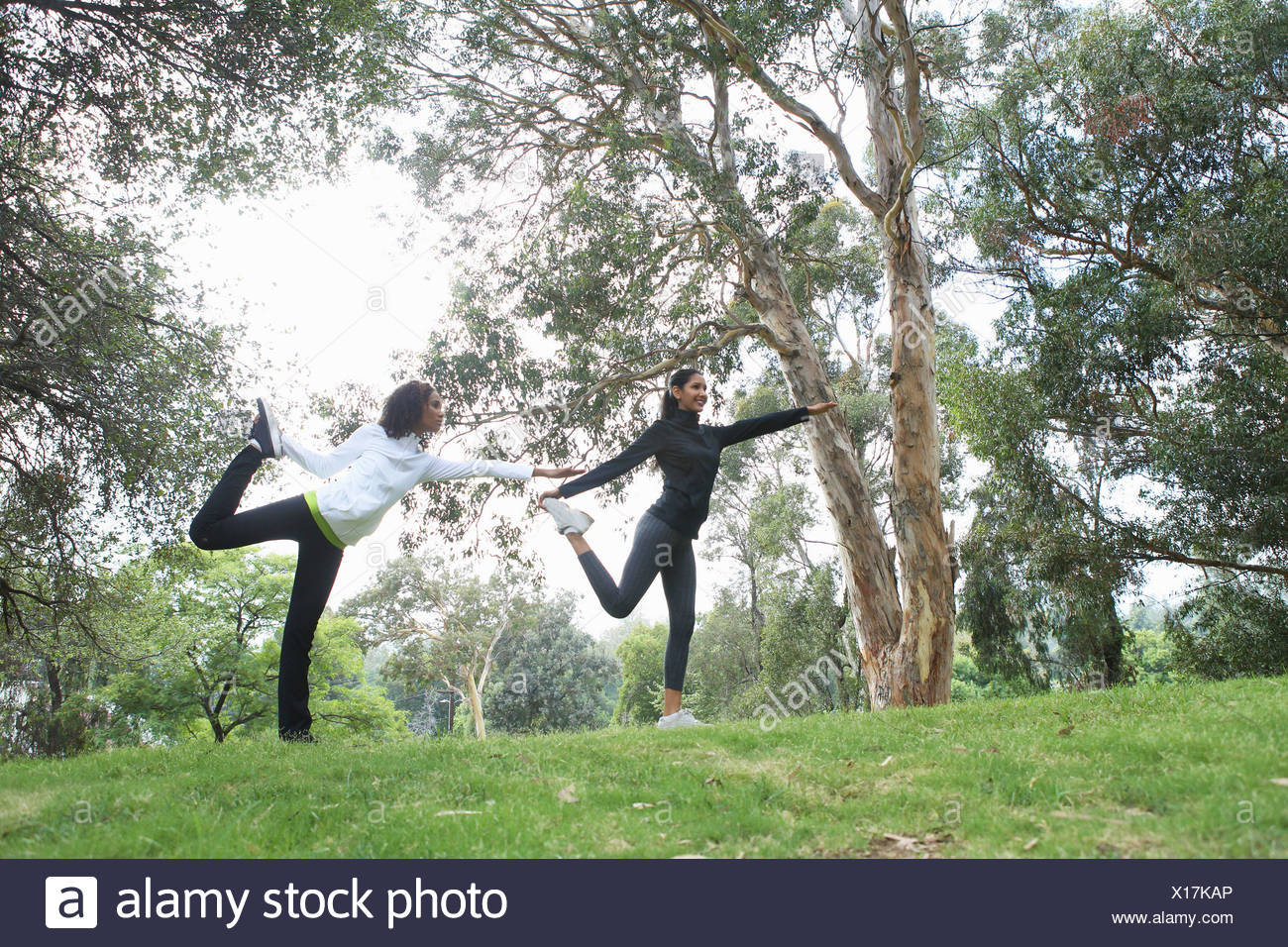 Mid adult and young woman stretching in park - Stock Image
