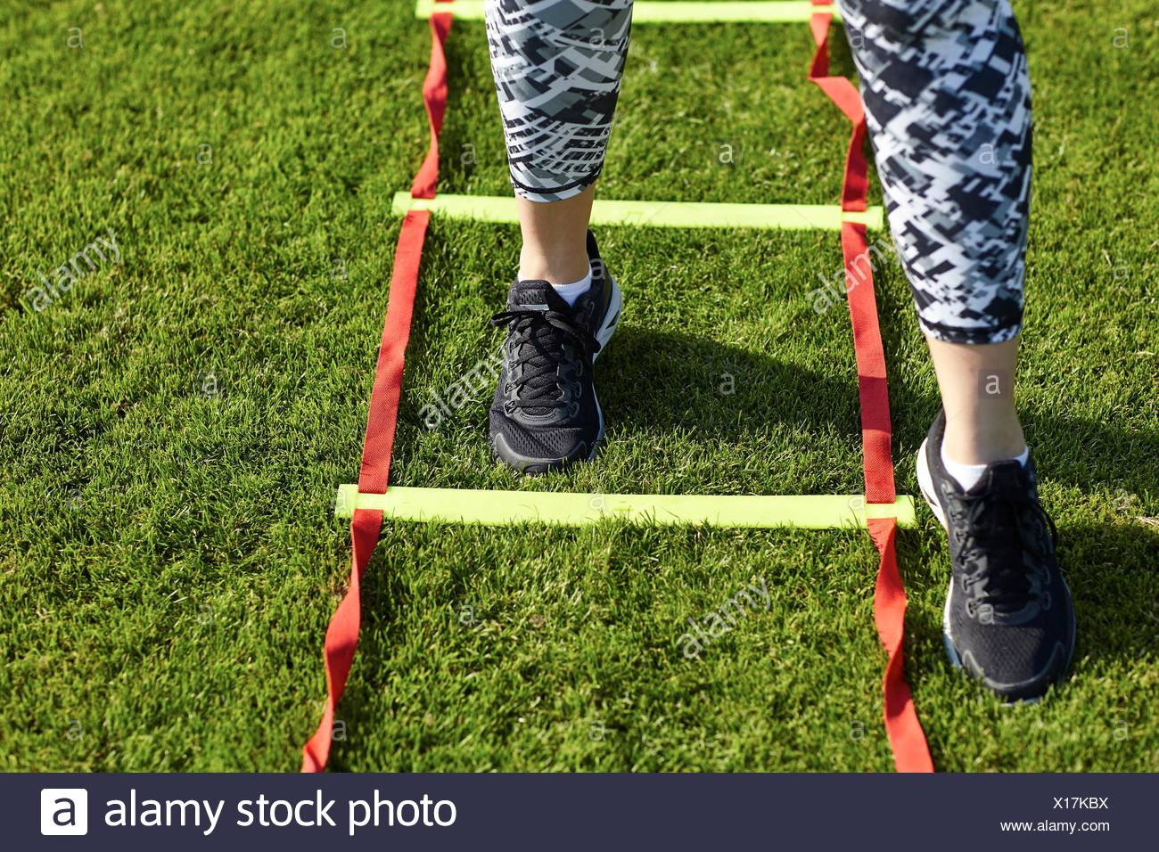 Feet of young woman training on agility ladder - Stock Image