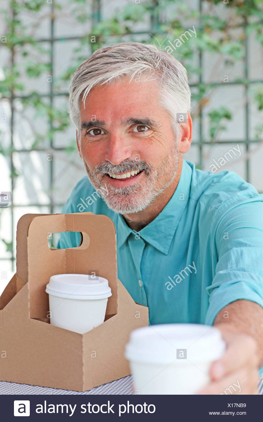 Businessman passing coffee to another person - Stock Image