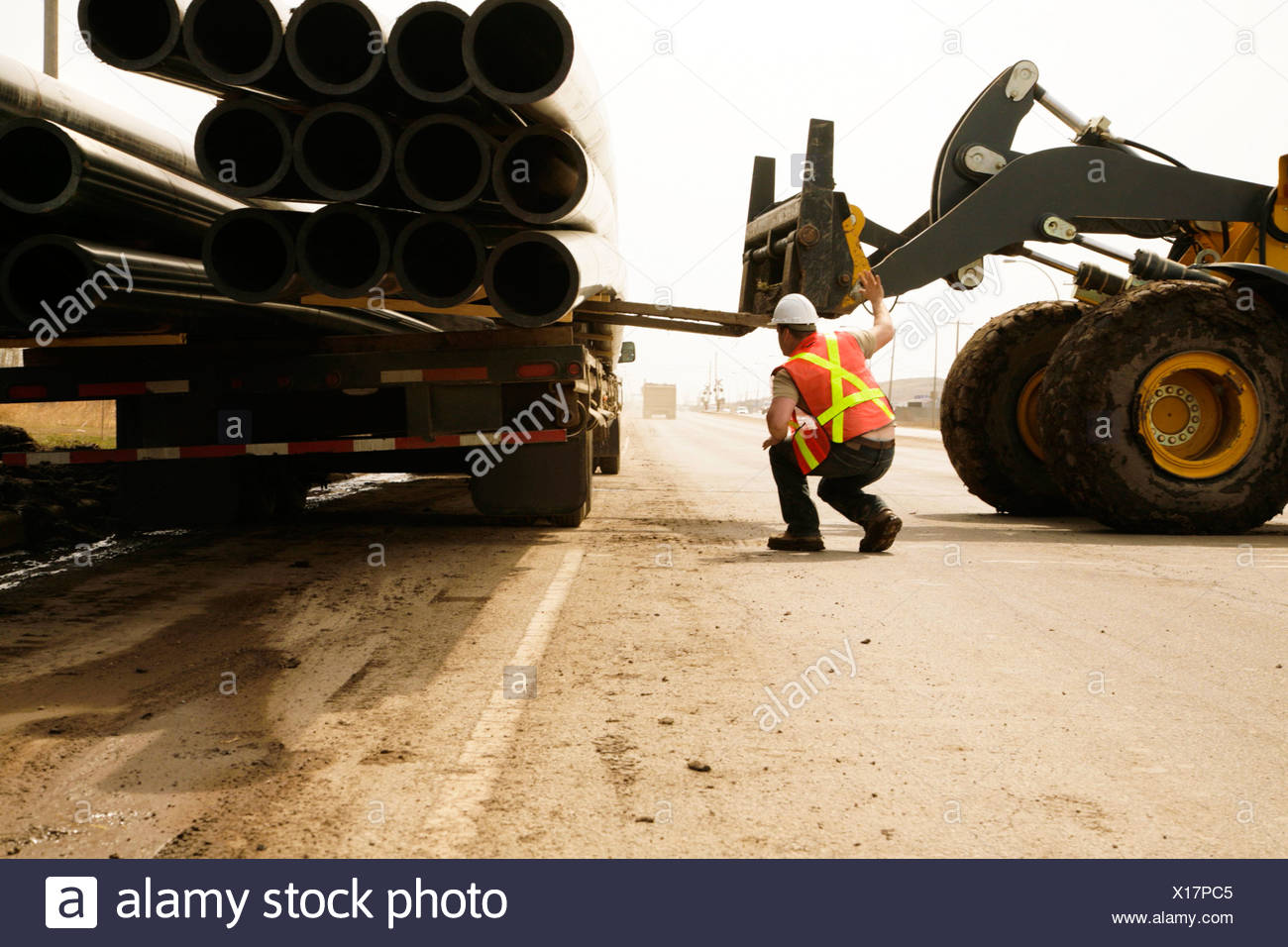 A Workman On Site Guiding A Forklift - Stock Image