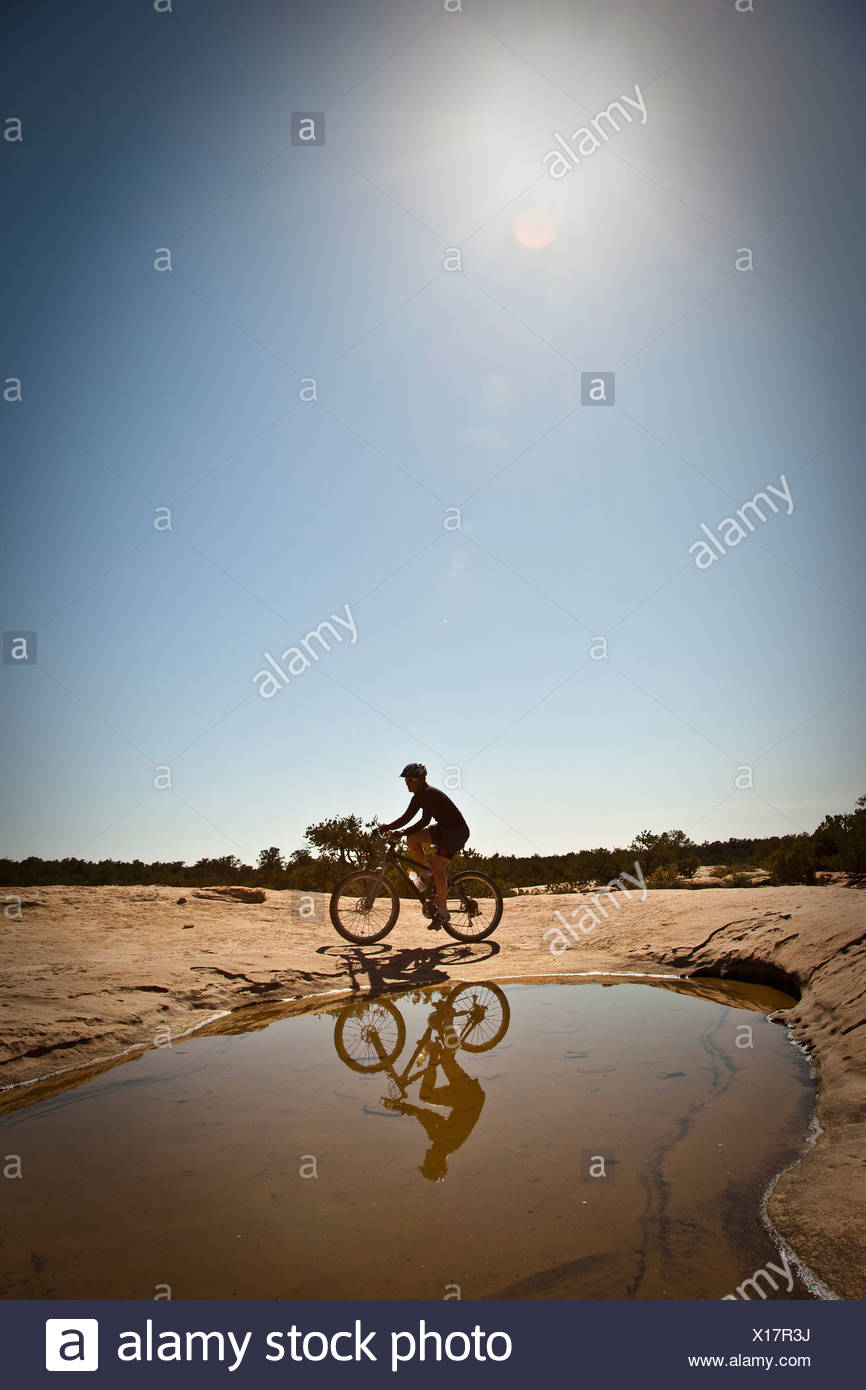 A woman mountain biking on slickrock in front of pool near Hurricane, Utah. - Stock Image