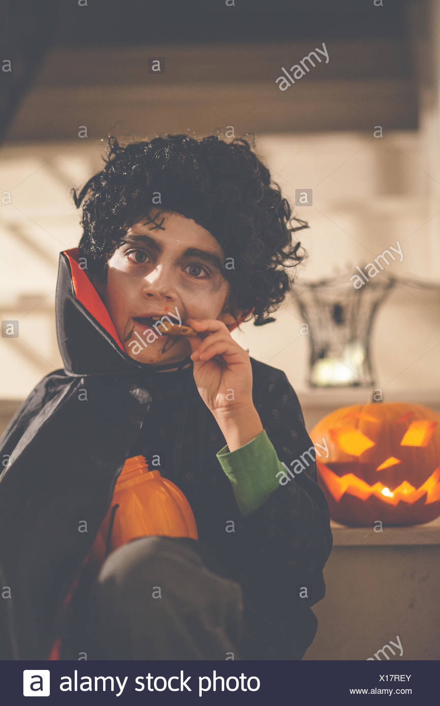 Boy dressed in Dracula Halloween costume eating a cookie - Stock Image