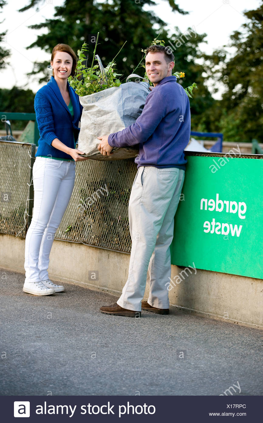 A mid-adult couple recycling garden waste - Stock Image