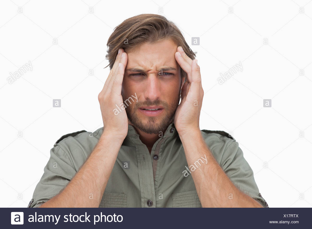 Man grimacing with pain of headache - Stock Image